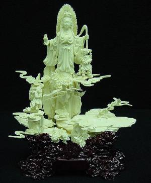 BONE SINGLE KWANYIN W/FLOWER KIDS (9627) This is a Cow Bone carving. All hand carved with lots of details. A kwanyin is carved in the center, together with flower kids. It represents Gods Blessing. Kwanyin is the famous female god in the east. Even today, people all over the world still believe in her.  Size: L:8in, W:4in, H:10in
