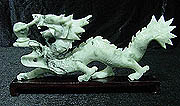JADE SINGLE DRAGON (LH24) This Dragon is carved from one solid piece of jade. It comes with a rosewood base. Very detailed carving.  SIZE: L: 12 in, W: 2 in, H: 6 in