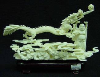 BUDDHA FIGHTING WITH DRAGON (9602) This is a elephant bone carving, all hand carved with lots of details. A buddha is standing in the sky, fighting with a dragon.  Size: L: 8 in, W: 3 in, H: 6 in. Click Here To See Big Picture.